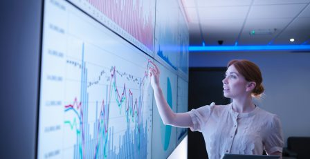 Businesswoman studying graphs on screens